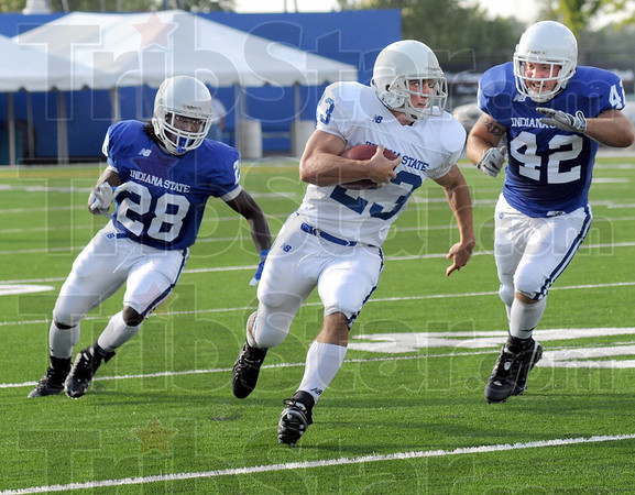 Catch and carry: Indiana State running back #23, Bryan Stefanik is chased after catching a pass during Thursday's Blue/White scrimmage.  Defending on the play is #28, Jerry Calvert and #42, Santino Davis.