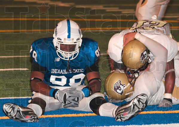 Tribune-Star/Joseph C. Garza<br /> We were so close: Indiana State linebacker Aaron Archie sits dejectedly next to Quincy quarterback Sam Donatucci, bottom,  as he celebrates his winning overtime touchdown with a teammate during the Sycamores' 26-20 overtime loss Thursday at Memorial Stadium.