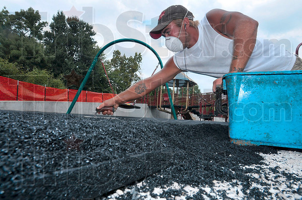 Tribune-Star/Joseph C. Garza<br /> Playground ground level: Playground Equipment Service's Paul Allen wasn't playing around Thursday as he smoothed over the first level of the new surface for the playground at Deming Park Thursday.