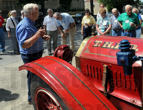 Tour stop: Tom Champion (blue shirt) talks about the 1910 Oldsmobile fire truck on display at the police and fire museum Thursday afternoon.