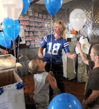 Food drive: Denny's general manager Eleanor Pesch gives balloons to kids as they leave the restaurant Friday afternoon. The restaurant is giving a twenty-percent discount to anybody wearing a Colts jersey and donating a non perishable food item for local food banks.