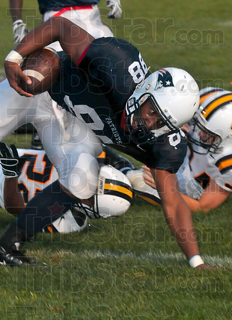 Tribune-Star/Joseph C. Garza<br /> Still going: Terre Haute North's Aaron Allen keeps his momentum after two Castle defenders tried to tackle him while he made a catch during the Patriots' game against the Knights Friday at North.