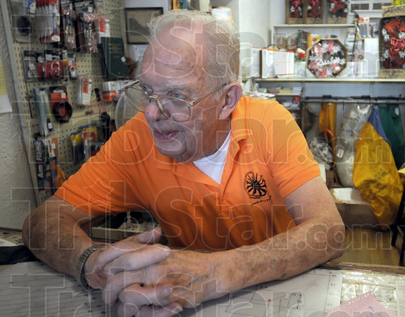 Social: Cecil Tilford sits in his variety store watching people walking past as they attend an ice cream social in 12 Points Saturday afternooon.