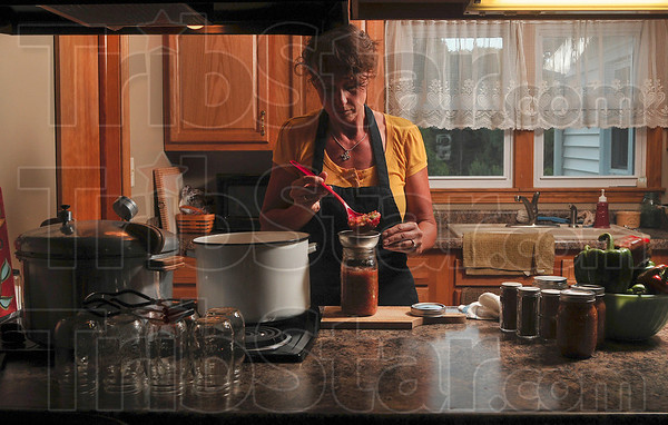 Tribune-Star/Joseph C. Garza<br /> Canned goodness: Angela Cripe pours freshly made salsa into a canning jar in her kitchen in Dennison, Illinois. Cripe grew the tomatoes, jalapenos, and onions in her garden.