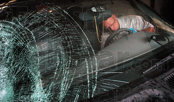 """Processed: Sheriff's crime scene investigator John Moats """"processes"""" a vehicle authorities believe was involved in a hit-and-run fatal accident. The vehicle owner, Eric D. Trinkle was arrested after police matched a side mirror left at the scene with the vehicle."""