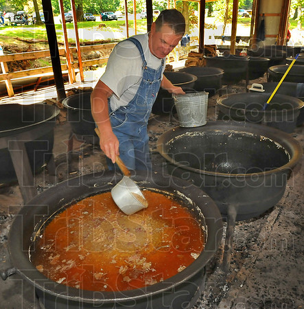 About gone: Carl Gregory ladles bean soup into a bucket at the Fontanet bean dinner Saturday. Some 2,000 pounds of beans and 300 pounds of bacon go into making the soup.