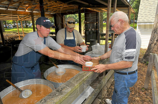 At your service: Pete Goda and his cousin Chad serve individual bowls of bean soup to Don Peters. For the first part of the dinner, beans are served  into pots and pans, five gallon buckets and ice cream pails. After that individual servings are given out until the soup's gone.