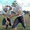 Hand-off: North quarterback Chris O'Leary (R) hands the ball to Ben King during Wednesday's practice session. At right coach Chris Barrett watches the action.