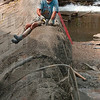 Tribune-Star/Joseph C. Garza<br /> Hands on approach: Bridgeton Mill owner Mike Rowe chisels away excess cement as he and other volunteers work on the dam in Bridgeton Wednesday.