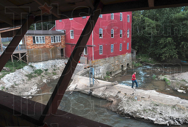 Tribune-Star/Joseph C. Garza<br /> View from the bridge: Volunteer Carl Redemske of Rockville walks along the dam near the Bridgeton Bridge Wednesday in order to complete more work on the structure with other volunteers.