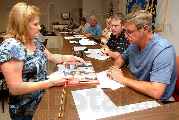 Documents: Bonnie Fuelle, who owns property in the neighborhood, presents photographs to Paul Mason and others on the Area Planning Commission she says relate problems she and friends see in regarding Mike's Auto Wrecking. She and others were hoping to stop the rezoning of part of their residential neighborhood.