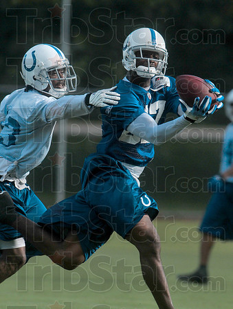 Tribune-Star/Joseph C. Garza<br /> On target: Indianapolis Colts wide receiver Reggie Wayne grabs a pass from quarterback Peyton Manning out of the reach of a defending teammate during the team's morning practice Tuesday at Rose-Hulman.