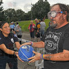 """Try again: Indiana State University's Tamara Watts hands the basketball to Dave Brown for another try at making a basket. Brown wears """"drunk goggles"""", eyewear that blurs and alters a persons' vision, approximating the effects of too much alcohol. The occasion was the National Night Out gathering at Fairbanks Park Tuesday evening."""