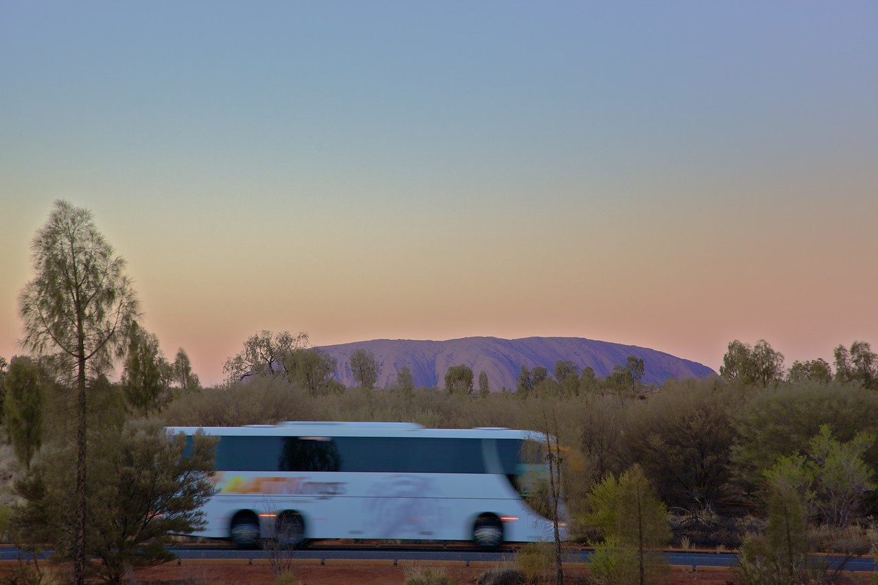 A tourist coach speeds in front of Ayers' Rock at sunrise.