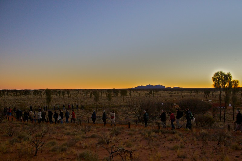Tourists head down to the 'Sounds of Silence' dinner in the desert near Ayers' Rock. In the background you can see the glow of the sun behind the Olgas.