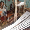 The weavers sit in a pit carved out to accommodate their legs.