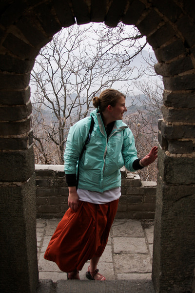 Tracy walks through a doorway and into the Great Wall of China.