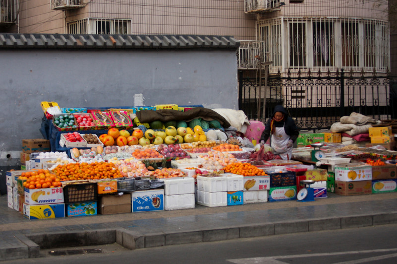 An enormous truckload of fresh fruit is laid out in a stand along one of the small hutongs.
