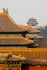 A distant temple stands on a hill overlooking the rooftops of the Forbidden City.