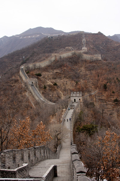 The Great Wall of China stretches off into the distance, dotted with tourists.