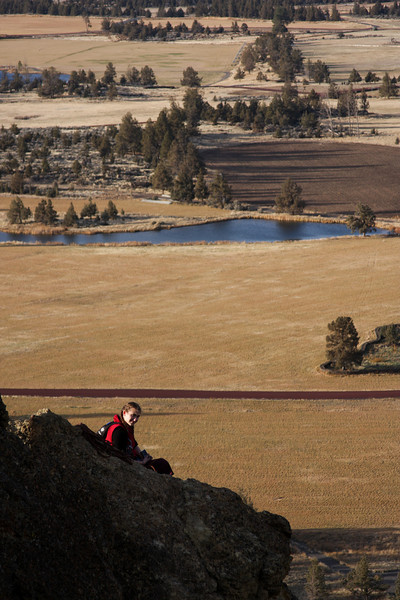 Tracy rests at the belay on <i>Wherever I May Roam 5.9</i> with farms dropping away behind.