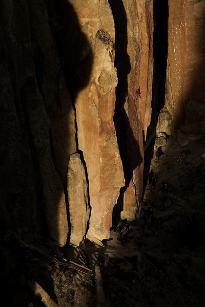 One climber among many is spotlighted by the late afternoon light on <i>Moondance 5.11c</i> at Smith Rock.