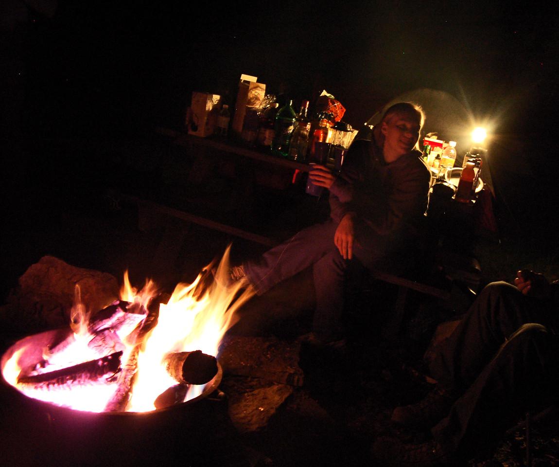 Rachel sits near the campfire