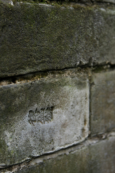 Brickwork bordering the garden's trails bears a marking in Chinese characters from ages ago.