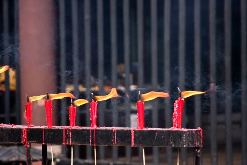 A row of candles melts into oblivion in front of one of the temple's many exhibits.