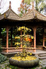 A large and thoroughly twisted bonsai tree sheds its autumn colors in front of a small pagoda in the garden.