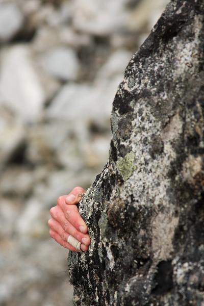 Katie Coan's taped fingers peek around a corner of rock high off the ground.