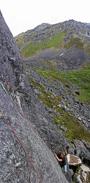 This is several photos stitched together of Melissa climbing <i>The Slot 5.7</i> with the sloping rocky hills of Archangel Valley in the background.