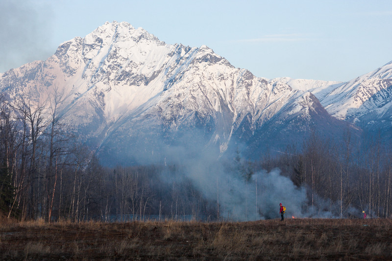 Sparse grass doesn't burn too well, giving off a light smoke in front of Pioneer Peak.
