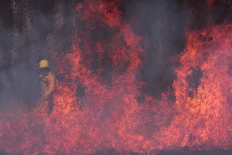 Firefighters shimmer in the heat waves beyond the burn.