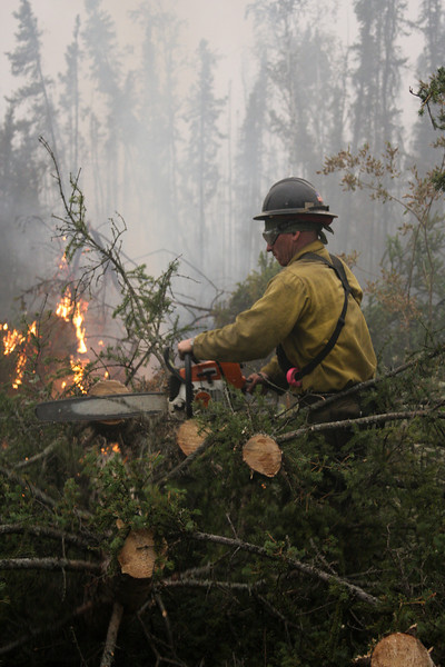 Some areas of the road were veritable minefields of falling trees.  Often, we would pass a car going the other direction and round a corner to find an impassible mass of debris just fallen into the roadway.  Here, Danny Clemons clears a tree from the road as its roots continue to burn.