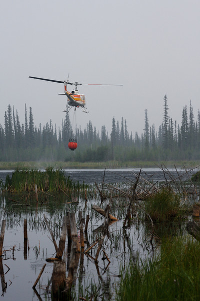 Its bucket filled, the chopper takes off again back to where it's hot.