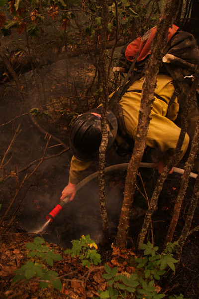 Danny Clemons puts some water on a hotspot in the woods.