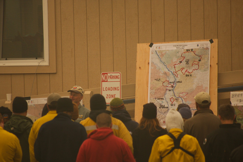 Briefing takes place each morning, and the heads of various crews working the fire get their assignments for the day.