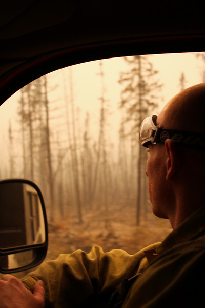 Danny Clemons watches the burned trees move by on a road patrol for fallen snags.