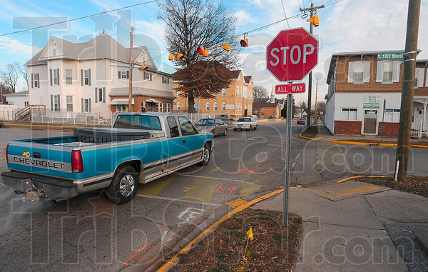 Tribune-Star/Joseph C. Garza<br /> Don't forget to stop: A motorist travels east after stopping at the new four-way stop at North 14th and Locust Streets Thursday.