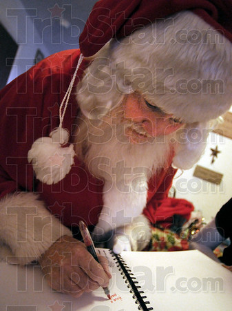 "Santa's message: Santa signs Sierra Coopers ""dream"" book during his visit to her Sunday afternoon in her Clinton, Indiana apartment."