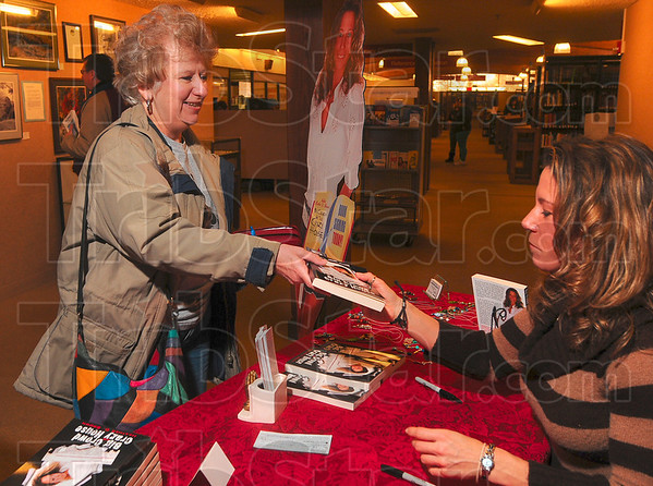 Tribune-Star/Joseph C. Garza<br /> Signed by the author: Author Heather Brown hands a copy of her book, Big Crowd at the Crazy House, to friend, Suzie Miles, after she signed it for Miles Saturday at the Vigo County Public Library.