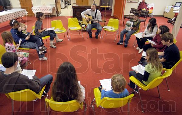 Guitar man: Assistant Rabbi Matt Cohen plays the guitar and sings during Sunday's meeting.