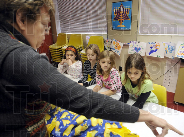 Here's how: Shirley Wormser shows Jennifer Garcia-Israel, Noam Waski, Mary Gatrell and Sia Skillman how to make the blankets during Sunday's event at the Temple Israel.