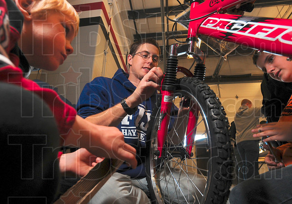 Tribune-Star/Joseph C. Garza<br /> Helping hands: Ty Englehart, left, and Austin Smith, right, sit ready to help Rose-Hulman student Bradley Seibert, 21, of Tulsa, Oklahoma, with the assembly of a bicycle for the Bikes for Tykes program Saturday on the Rose-Hulman campus.