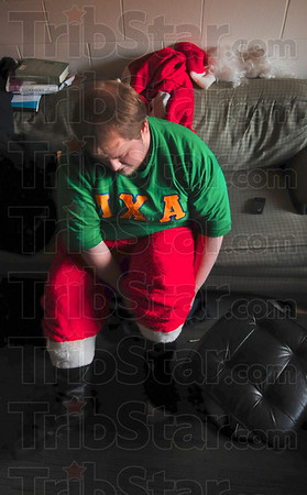 Tribune-Star/Joseph C. Garza<br /> Now we don our Santa apparel: Santa's helper and Lambda Chi Alpha member Ben McNees, a Rose-Hulman sophomore, puts on his jolly old elf outfit on in his room before handing out toys Saturday at the Rose-Hulman fraternity.