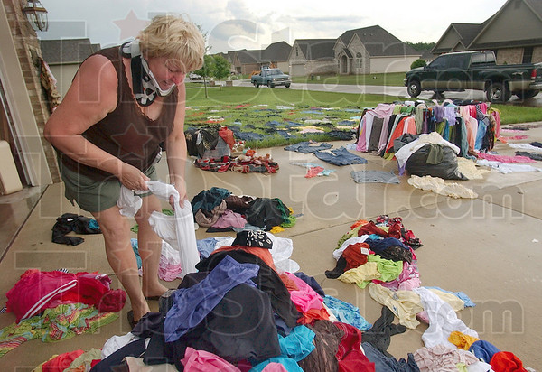 Tribune-Star file photo/Joseph C. Garza<br /> So much for drying them: Onalee Myles looks through her soaked articles of clothing Monday, June 9, 2008 at her home in Oakridge subdivision. Myles tried to dry the pieces of clothing in Monday's sun after they were soaked by flooding in her house but her efforts were ruined by more rain later in the afternoon.