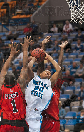Stiff defense: Indiana State's Dwayne Lathan tries to score against two Ball State defenders, including Malik Perry (1), in the second half of the Sycamores' 68-63 loss Wednesday at Hulman Center.