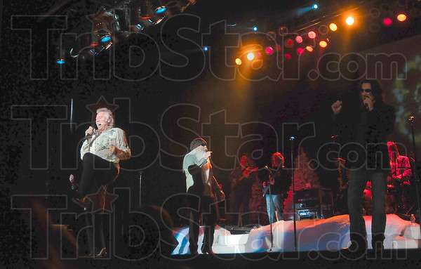 """Tribune-Star/Joseph C. Garza<br /> Back...in the spotlight: Joe Bonsall accentuates the end of a line with a kick as he and his fellow Oak Ridge Boys open their set with """"American Made"""" Wednesday in Tilson Auditorium."""