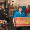Tribune-Star/Joseph C. Garza<br /> Ready to be delivered: Volunteer Takoda Sons, 13, carries a completed gift basket to a truck at the Tribune-Star Production Center Wednesday.